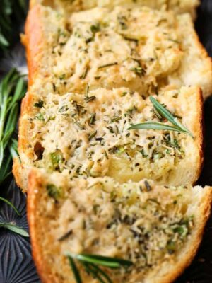 Rosemary Asiago Garlic Bread sliced on a sheet pan