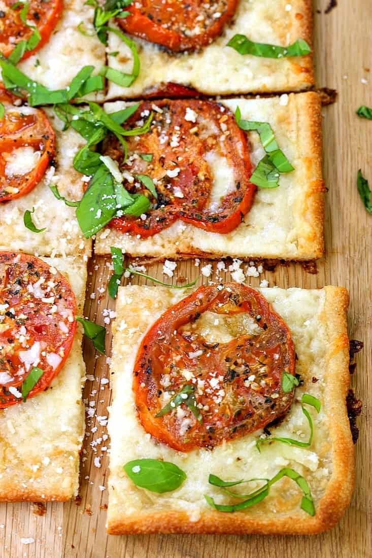 Roasted Tomato Basil Pizza sliced into squares on a cutting board