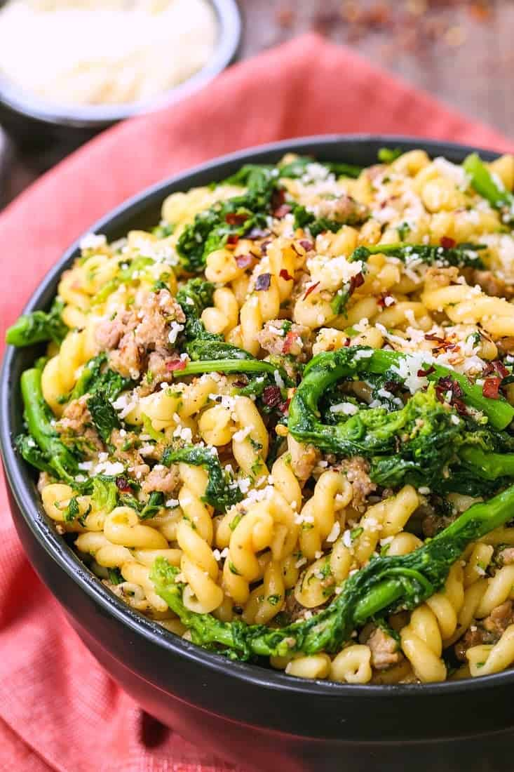 Pasta with Sausage and Broccolini in a black bowl with parmesan cheese on the side