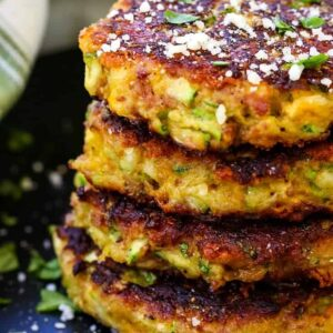 bacon zucchini cakes stacked on a black plate