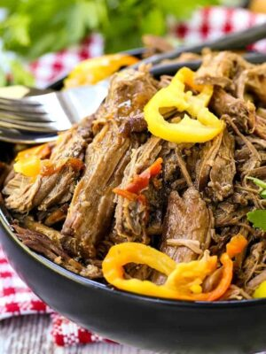 Slow cooker italian beef that's shredded in a black bowl