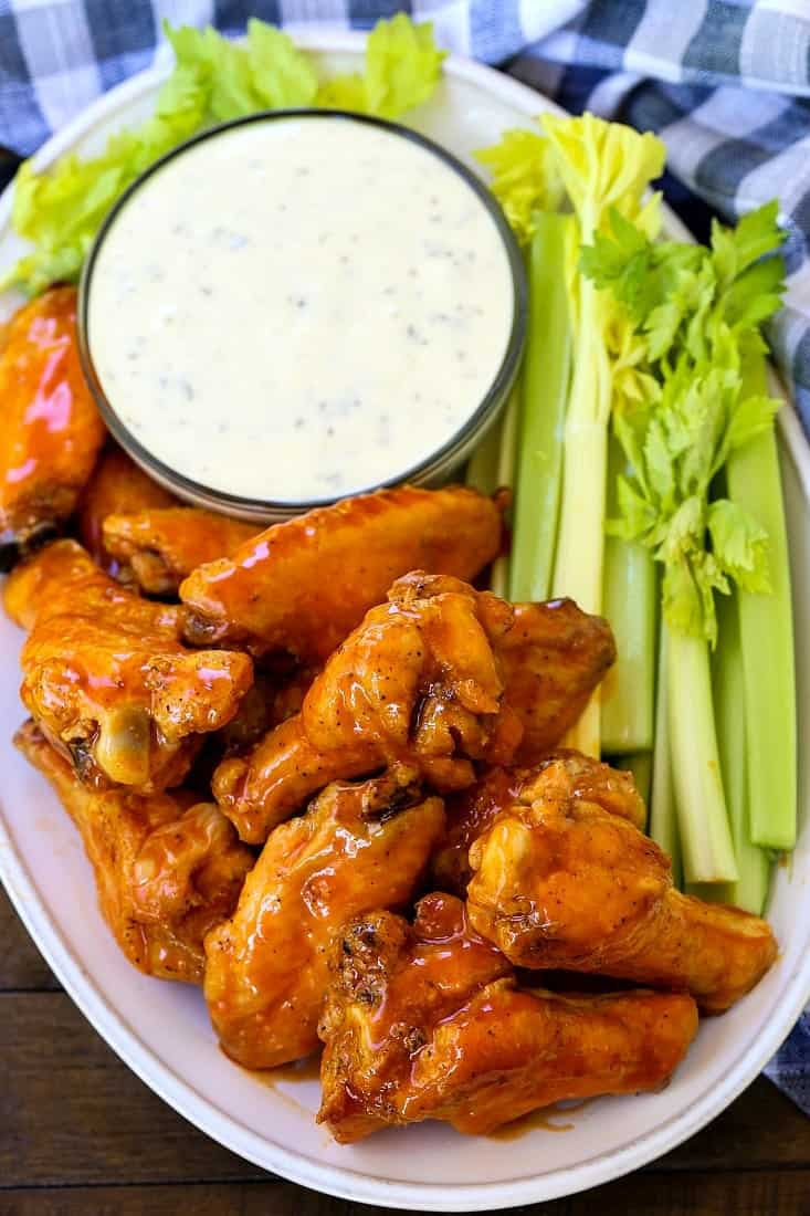 buffalo chicken wings on a platter with celery sticks and ranch
