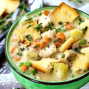 chicken pot pie soup in a green bowl with spoons