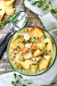 chicken pot pie soup with spoons on a wooden board
