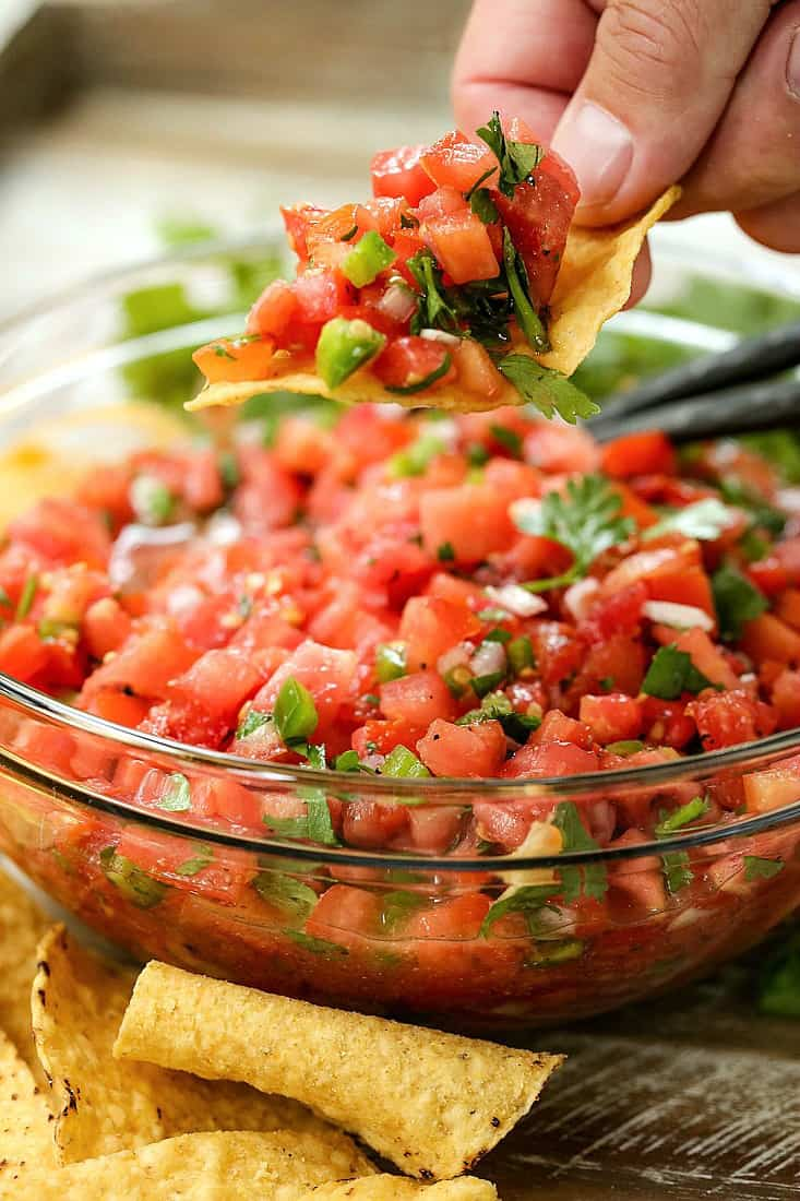 pico de gallo recipe in a bowl with chips on the side