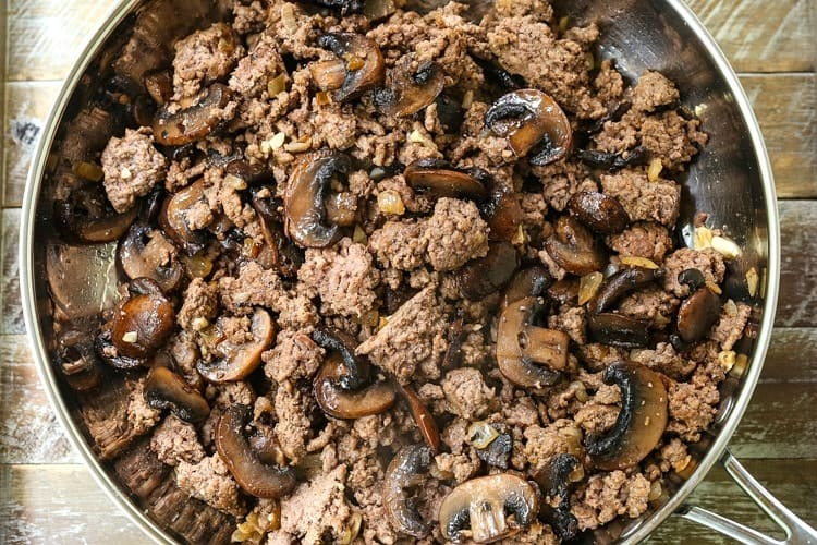 ground beef and mushrooms in a skillet on a wooden board
