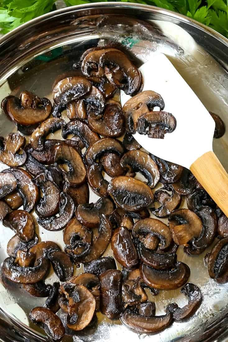 mushrooms browning in a skillet with a spatula