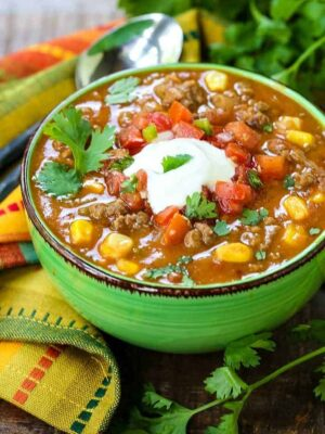 beefy taco soup in a green bowl with a colorful napkin