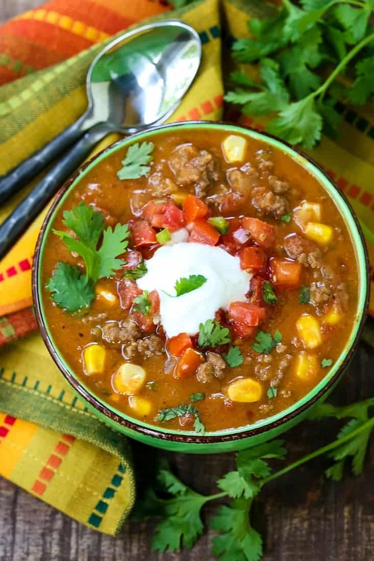 Beefy taco soup in a bowl with a colorful napkin and a spoon