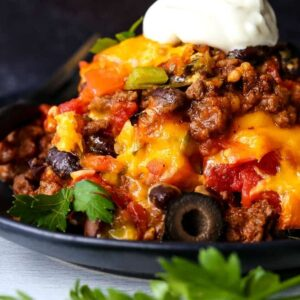 taco casserole on a black plate with sour cream