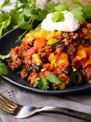 fiesta taco casserole on a black plate with cilantro