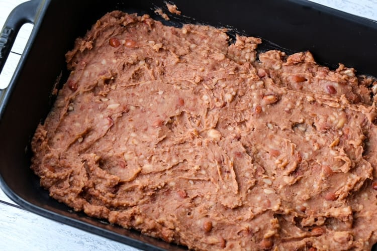 black casserole dish with refried beans on the bottom