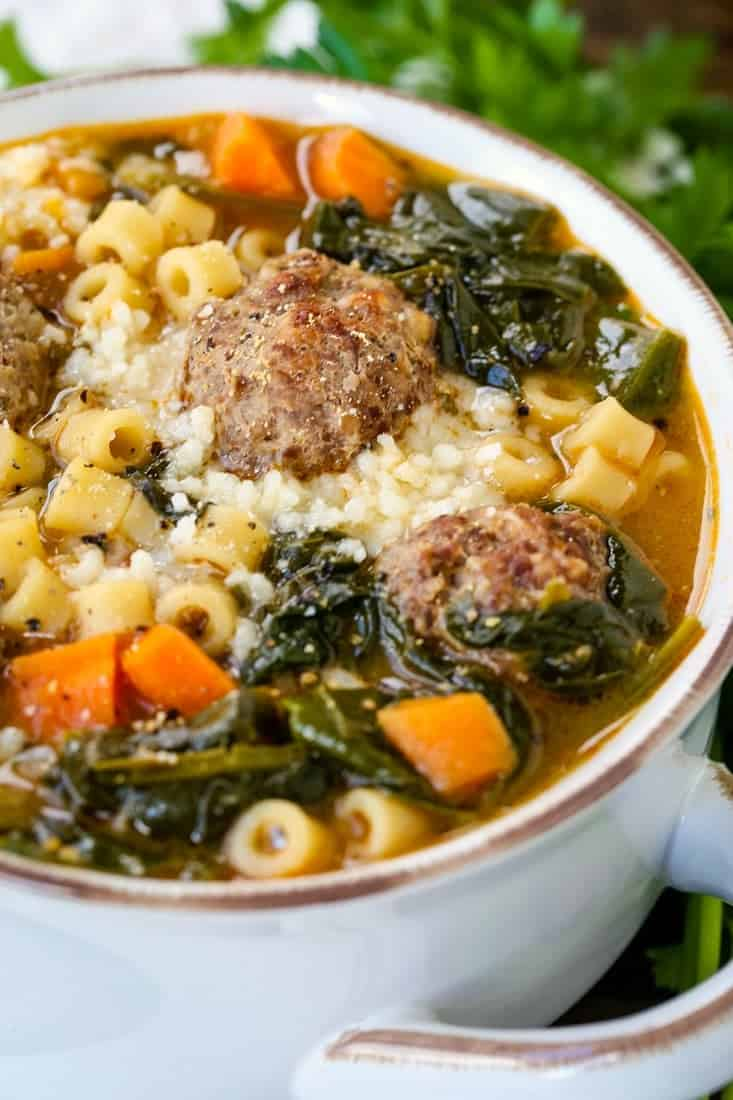 soup in a white crock with meatballs, pasta and spinach