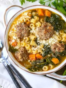 italian wedding soup in a white bowl with black spoons