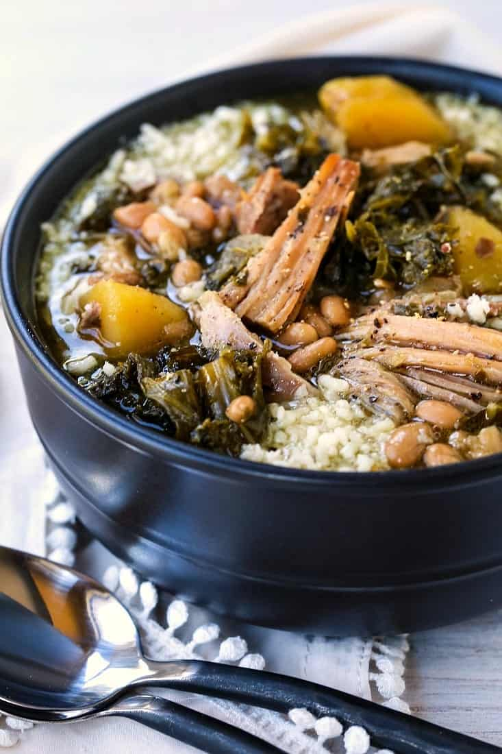 Slow Cooker Italian Pork Stew in a black bowl with parmesan cheese