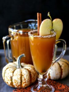 slow cooker spiked cider cocktail with pumpkins in the background