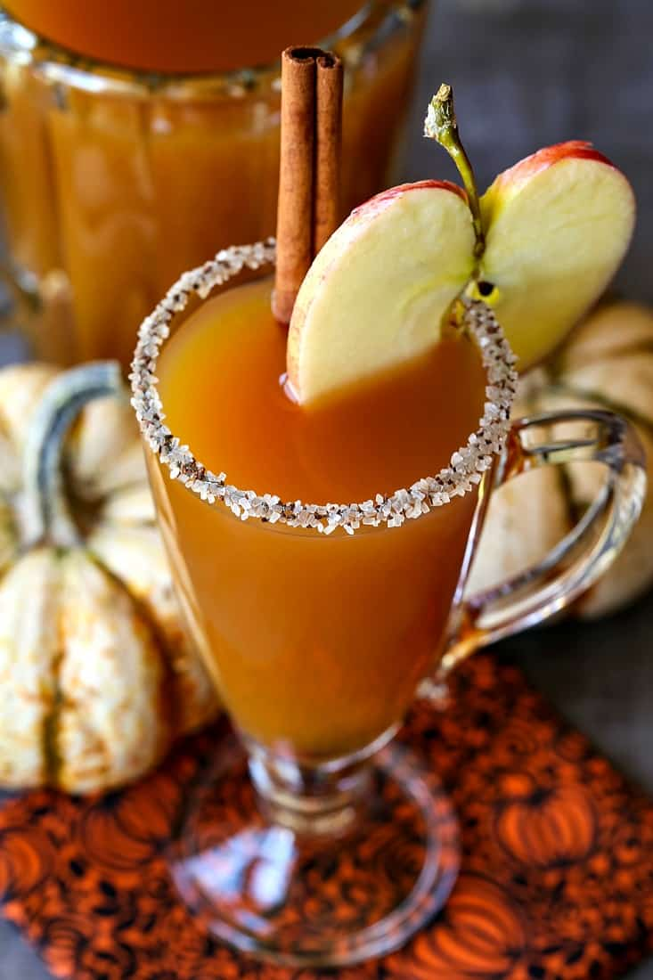 slow cooker apple cider cocktail with a sugared rim