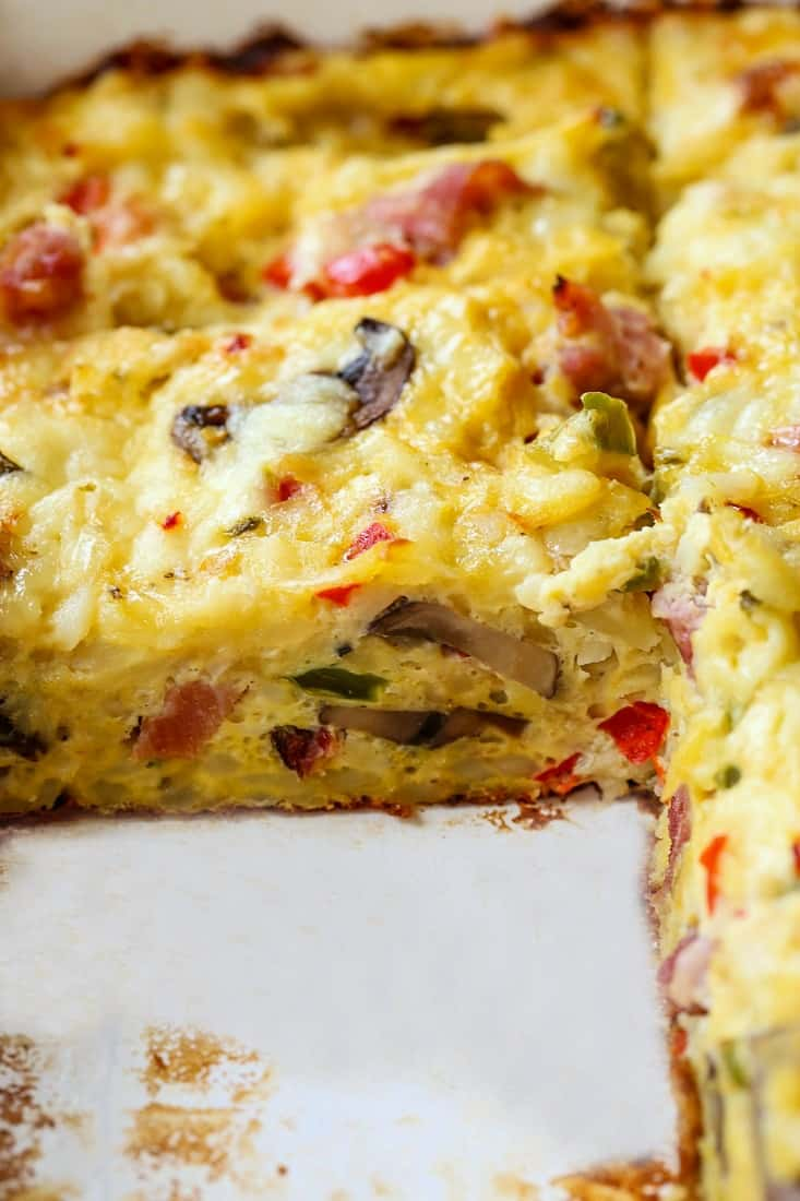 western hash brown casserole recipe in a baking dish with a slice out
