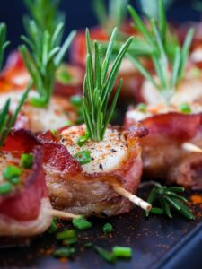 scallops wrapped with bacon and a rosemary garnish