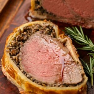 a slice of beef wellington on a board with rosemary