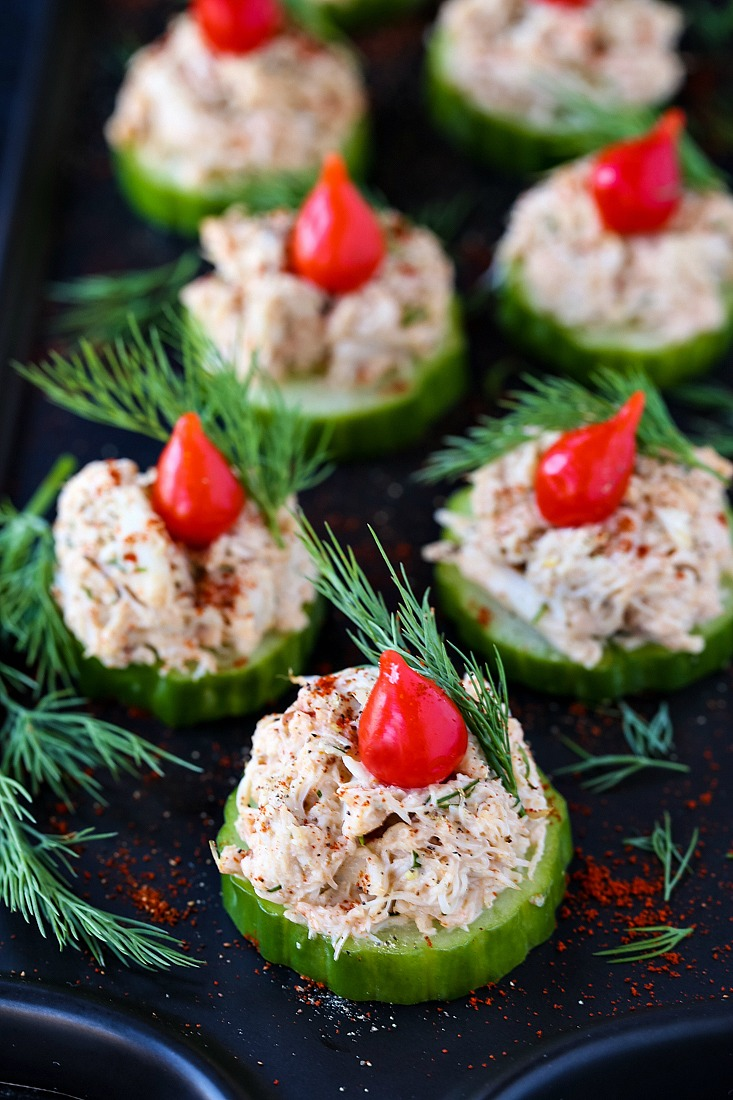 crab salad appetizers on a black platter with fresh dill