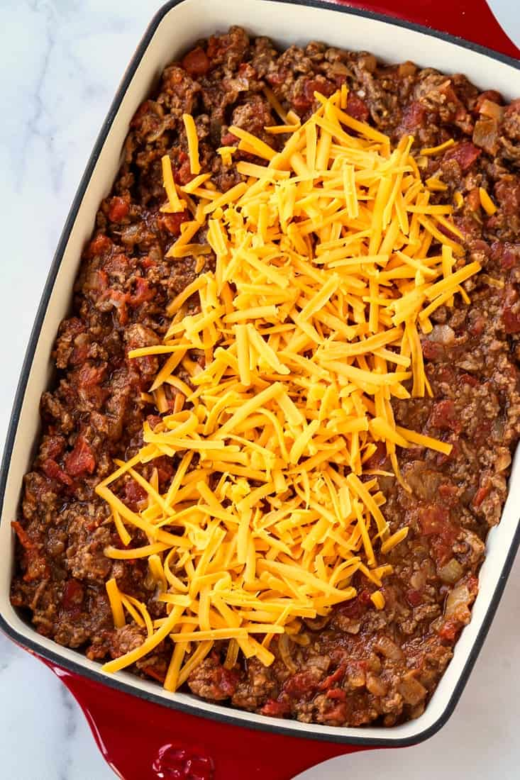 Cheeseburger casserole filling with shredded cheese on top