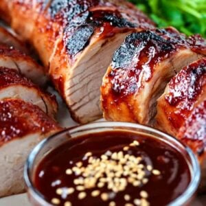 sliced pork tenderloin recipe with a cup of sauce and sesame seeds
