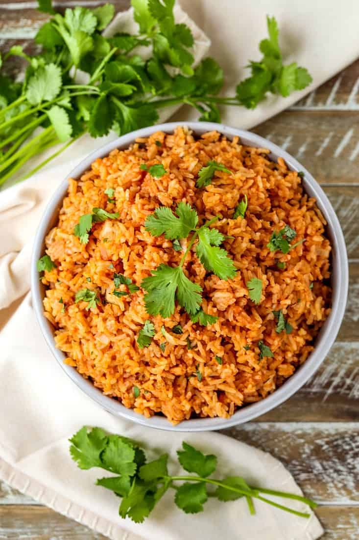 Spanish rice in a bowl with cilantro on a wood board