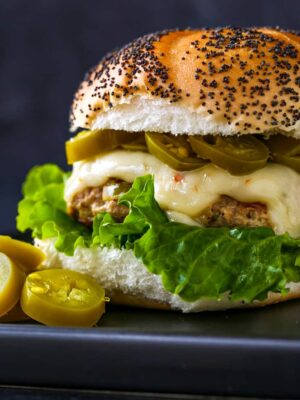 Turkey burger recipe with lettuce, cheese and jalapeños on a poppy seed bun