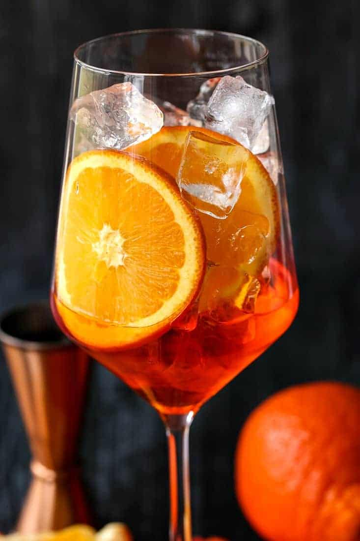 Aperol in a wine glass with ice and oranges