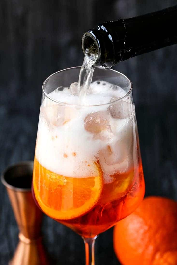 Prosecco being poured into a glass with Aperol