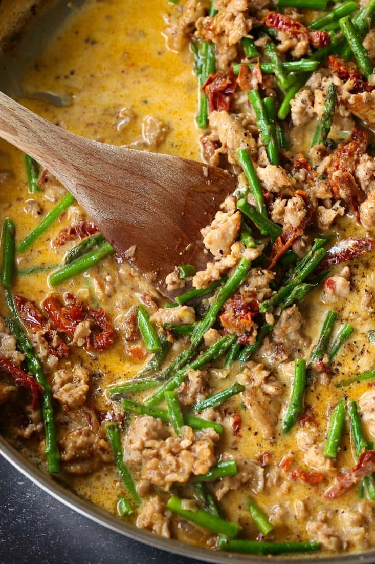 Sauce in skillet with sausage, asparagus and sun dried tomatoes for pasta recipe