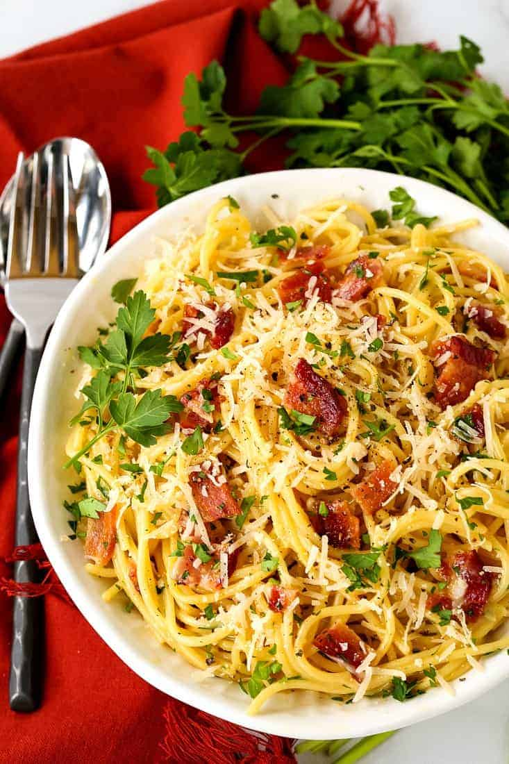 Pasta carbonara in a white bowl with a fork and spoon