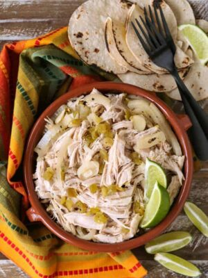 Shredded chicken in a bowl with limes