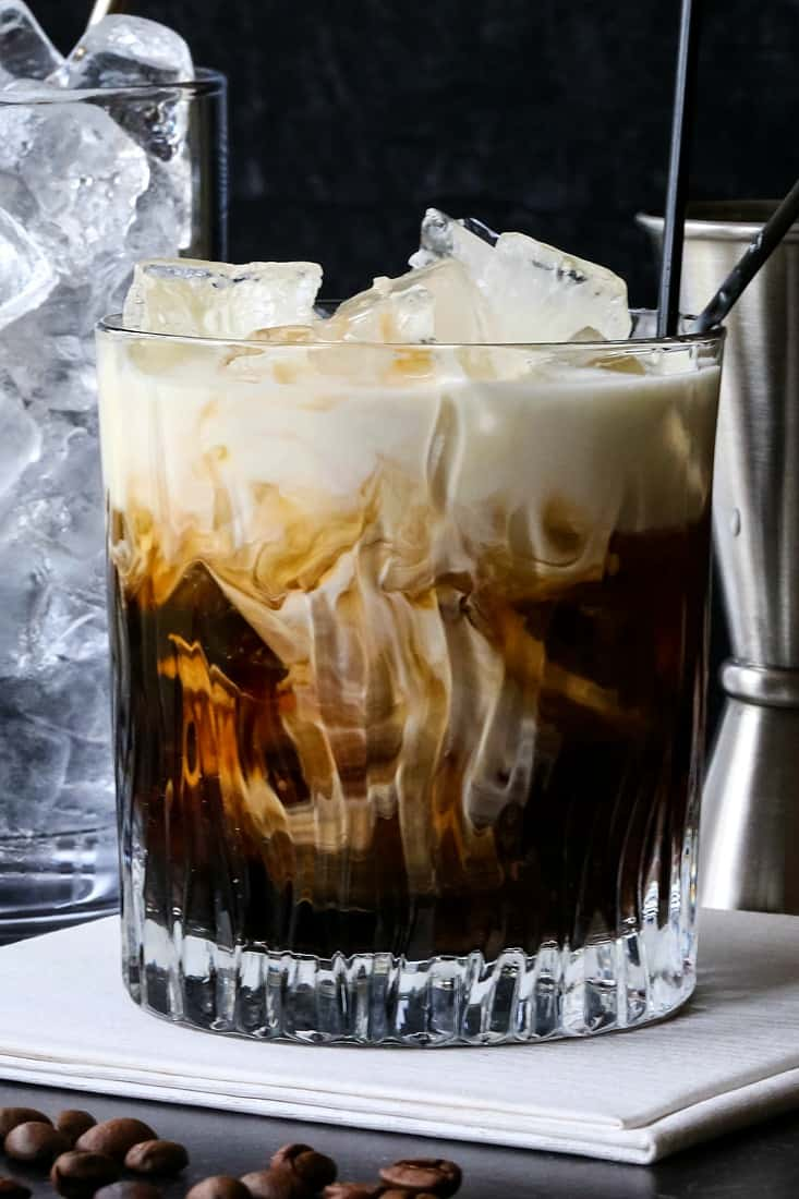 White Russian drink with a glass pitcher full of ice