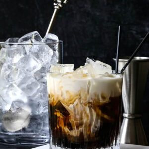 A White Russian cocktail with a pitcher of ice in the background