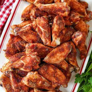 Seasoned baked chicken wings on a platter