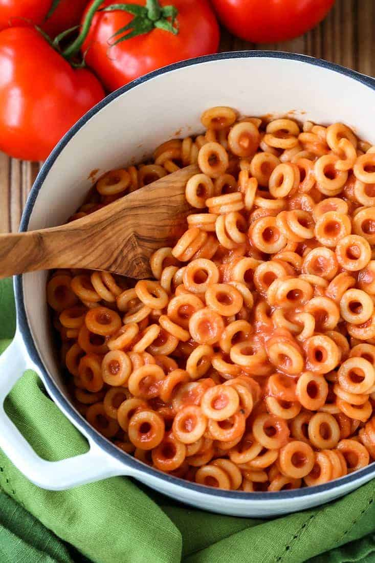 Spaghettios in a white pot with a wooden spoon