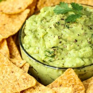 Easy Guacamole recipe in a bowl with fresh pepper and chips