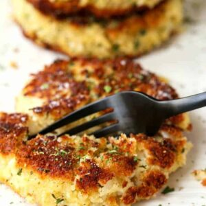 potato cakes on a plate with a black fork