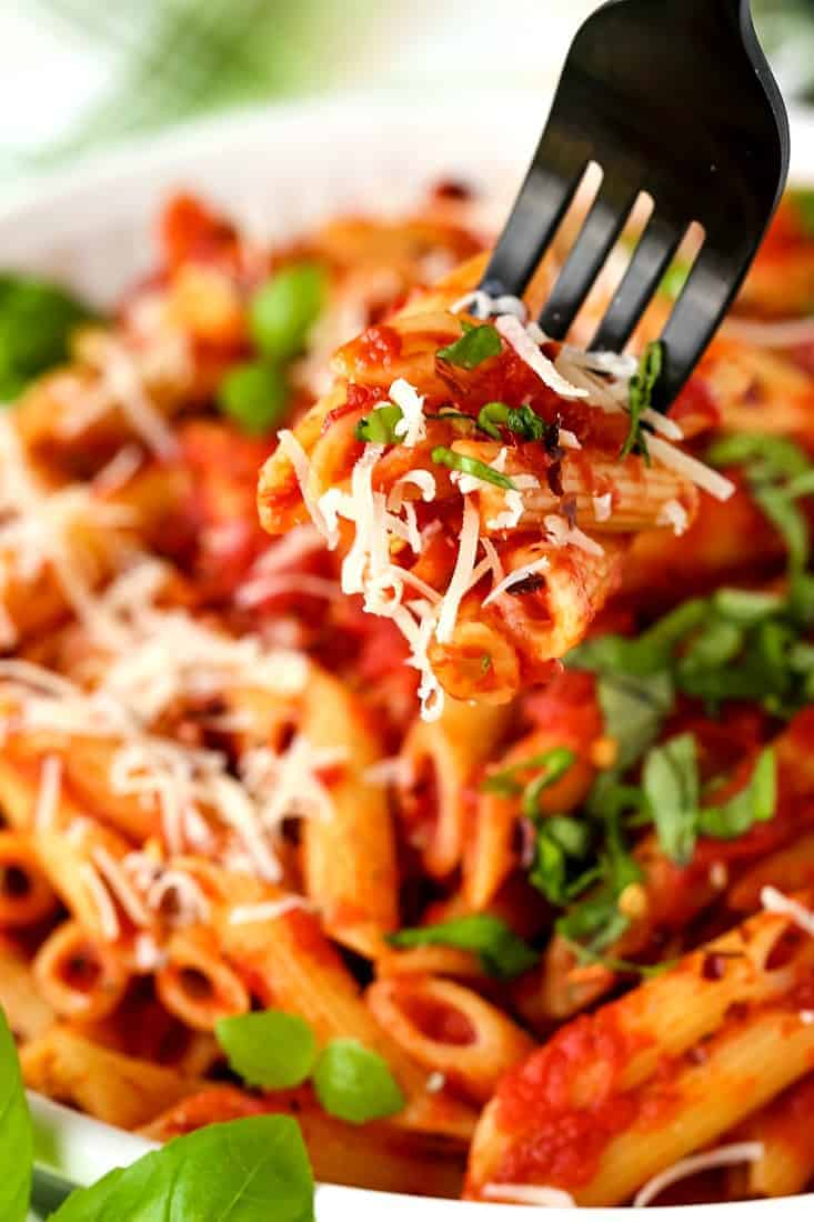 Penne arrabbiata with shredded parmesan cheese and fresh basil