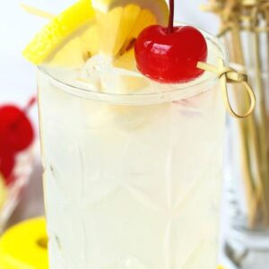 A Tom Collins cocktail with a lemon wedge and a cherry for garnish