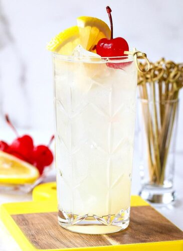 Tom Collins in a glass with lemon and cherry garnish