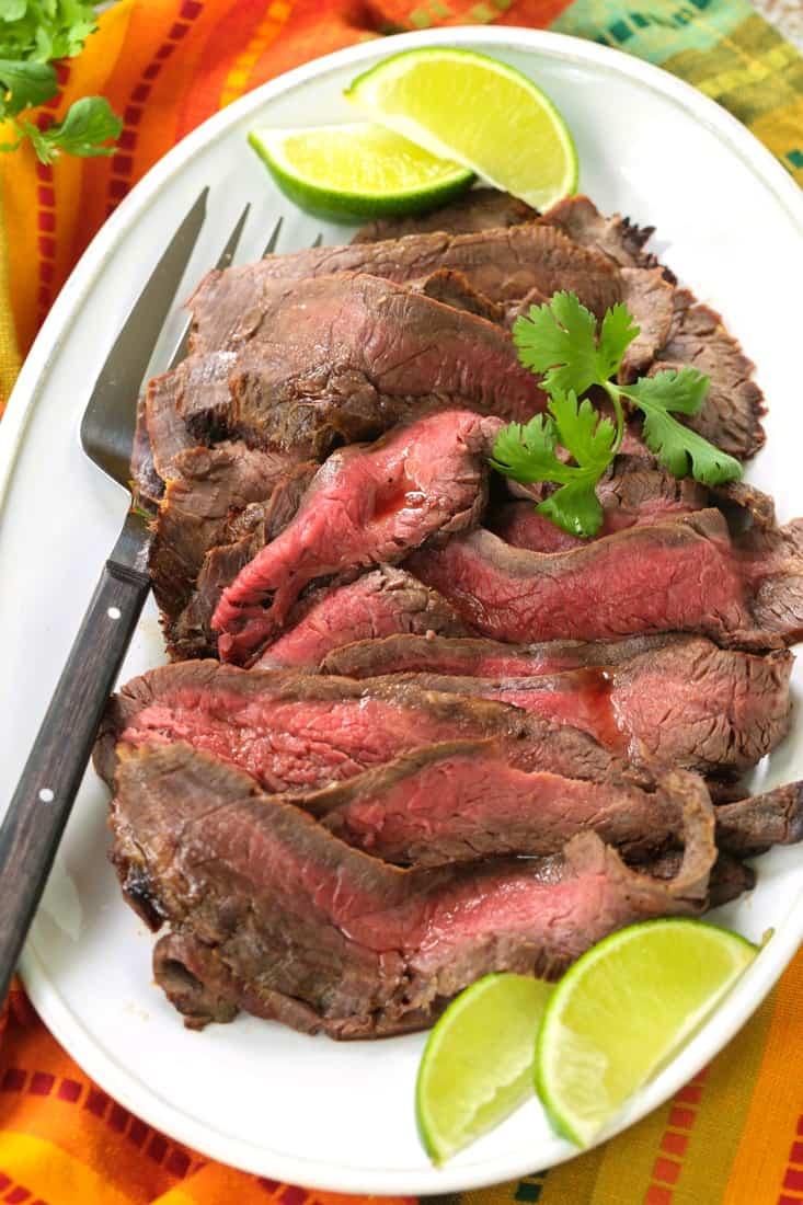 Flank steak on a platter with Fiesta Steak Marinade