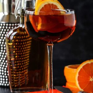 Sidecar cocktail with shaker and orange garnish