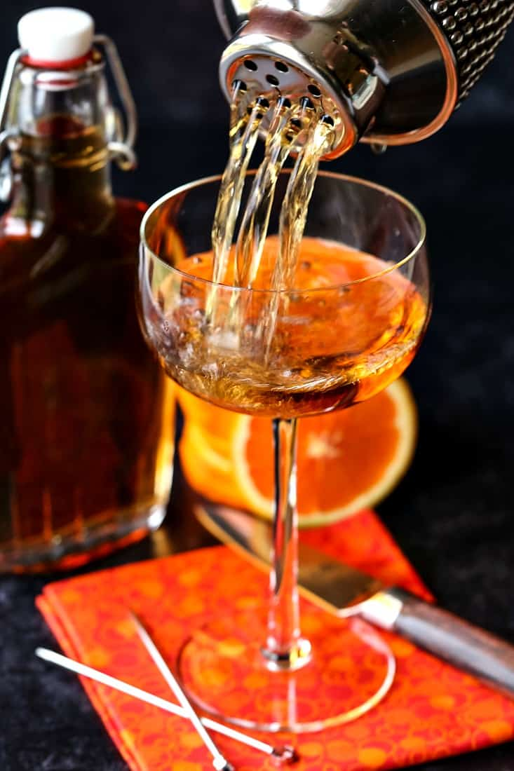 Amaretto sidecar drink being poured from cocktail shaker