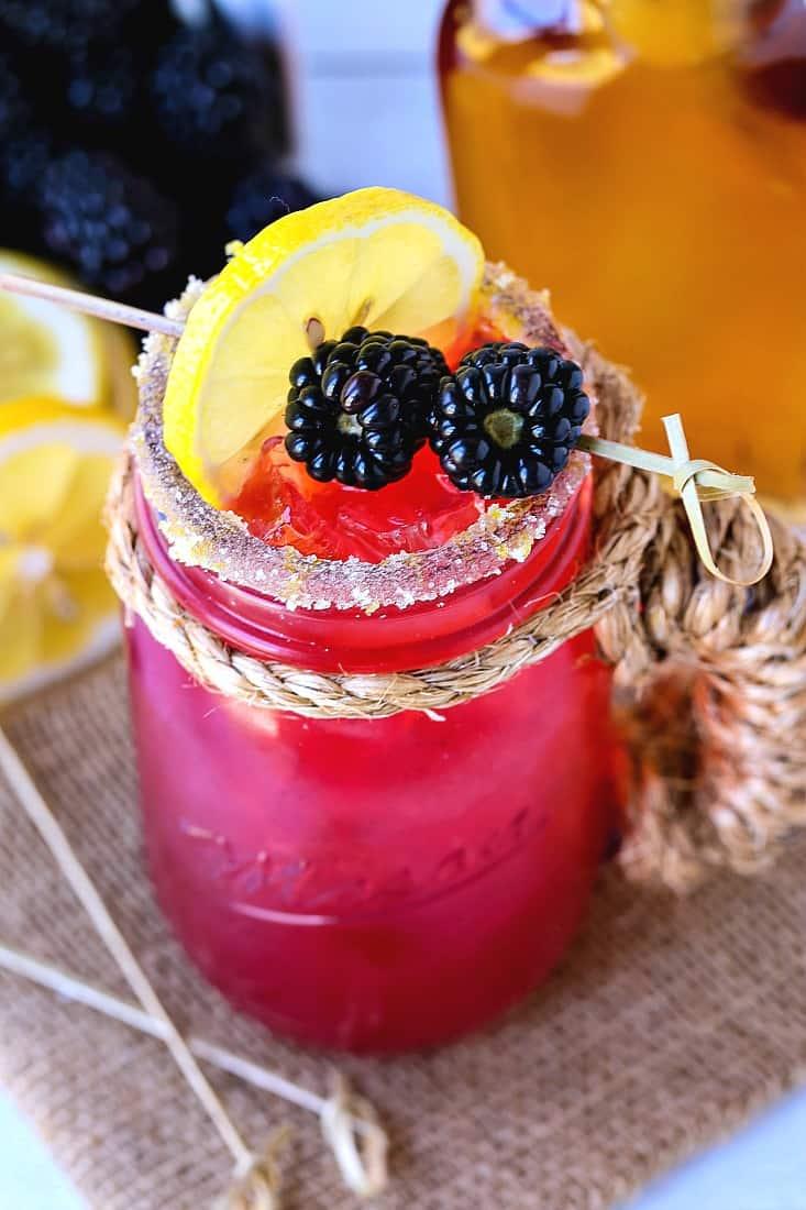 Bourbon lemonade with blackberries and lemon slice for garnish