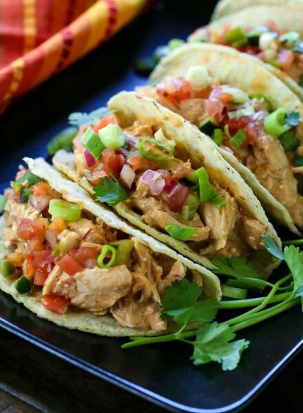 taco shells with creamy salsa chicken filling on black plate