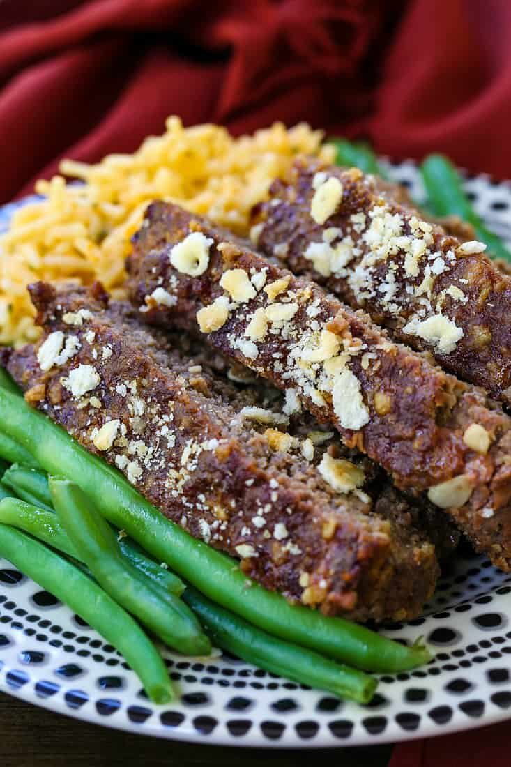 Slices of meatloaf stacked on a plate with green beans