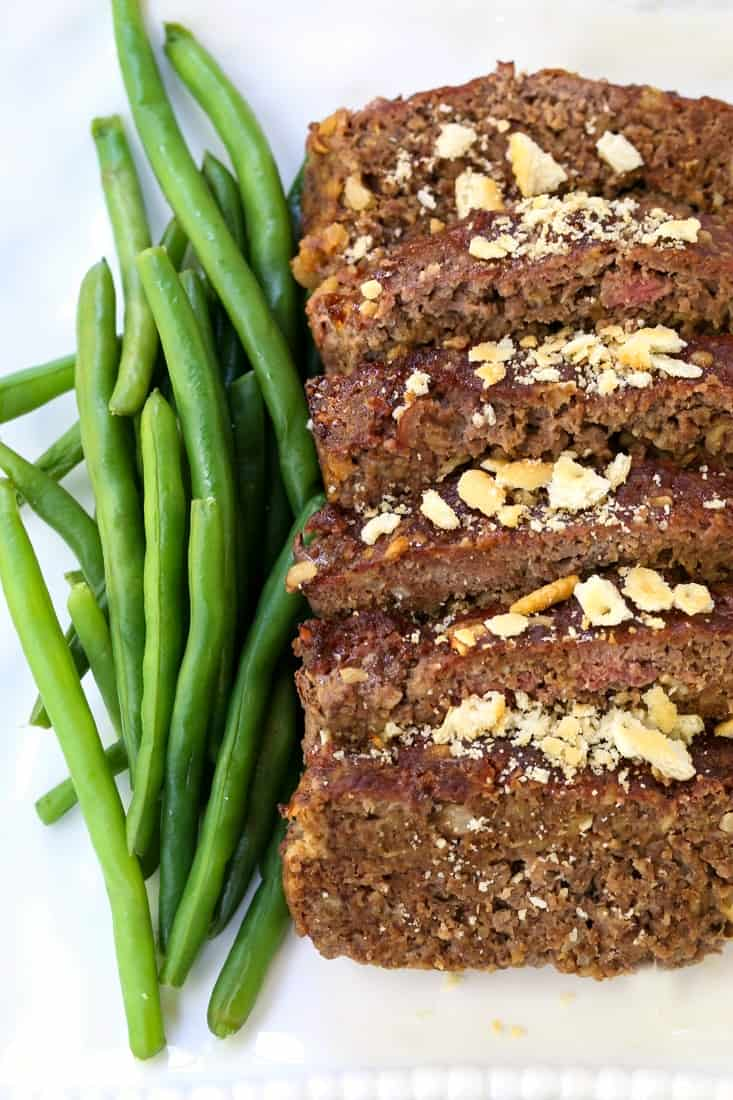 Ground beef meatloaf recipe on plate with green beans